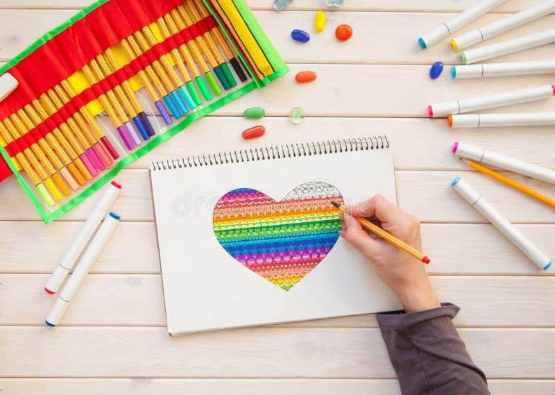 La fille dessine la carte postale de marqueurs avec un coeur de couleur Beaucoup marque lumineuse photo stock