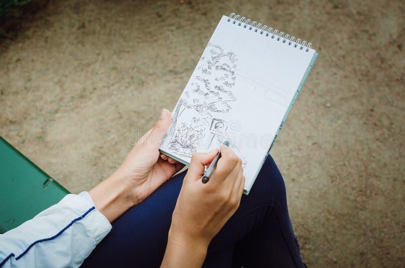 La fille dessine dans un carnet Remet le plan rapproché illustration stock