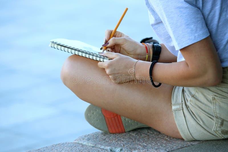 La fille dessine dans un carnet se reposant sur le trottoir photos stock