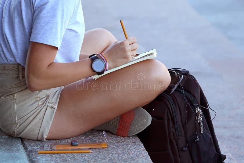 La fille dessine dans un carnet se reposant sur le trottoir photos libres de droits