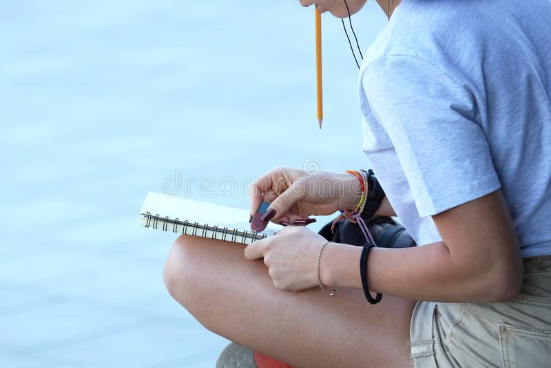 La fille dessine dans un carnet se reposant sur le trottoir images libres de droits