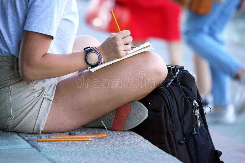 La fille dessine dans un carnet se reposant sur le trottoir image libre de droits