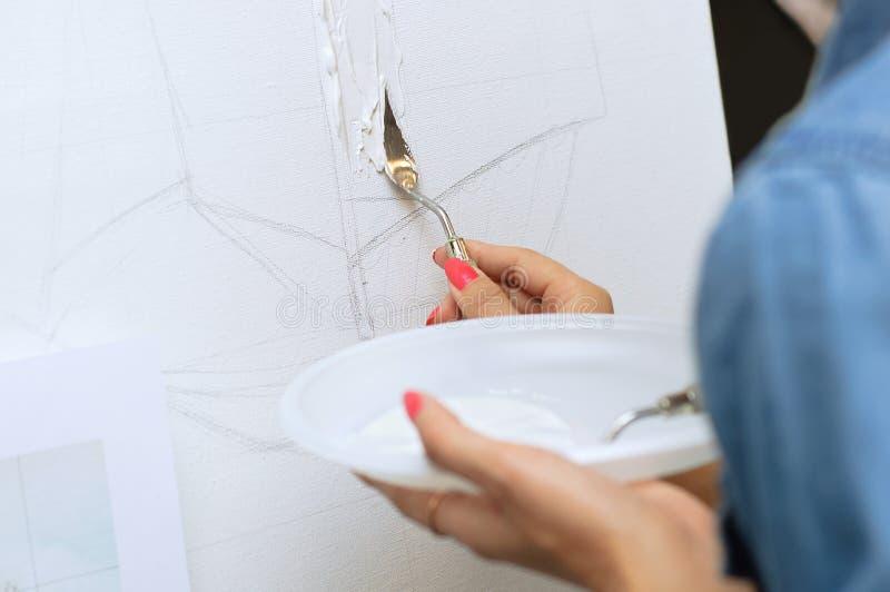 la fille dessine sur la toile dans la technique du couteau de palette Plan rapproché photos stock