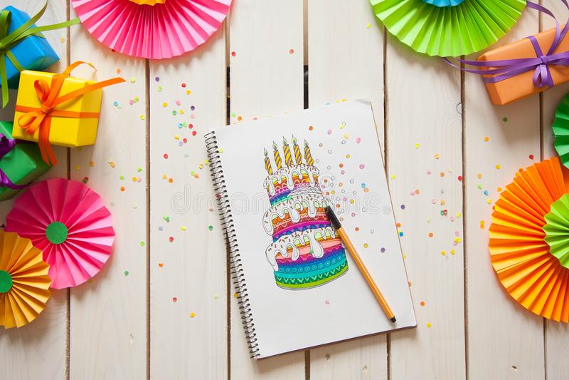 La fille dessine un gâteau avec les marqueurs colorés lumineux Cadeaux, rosett photographie stock