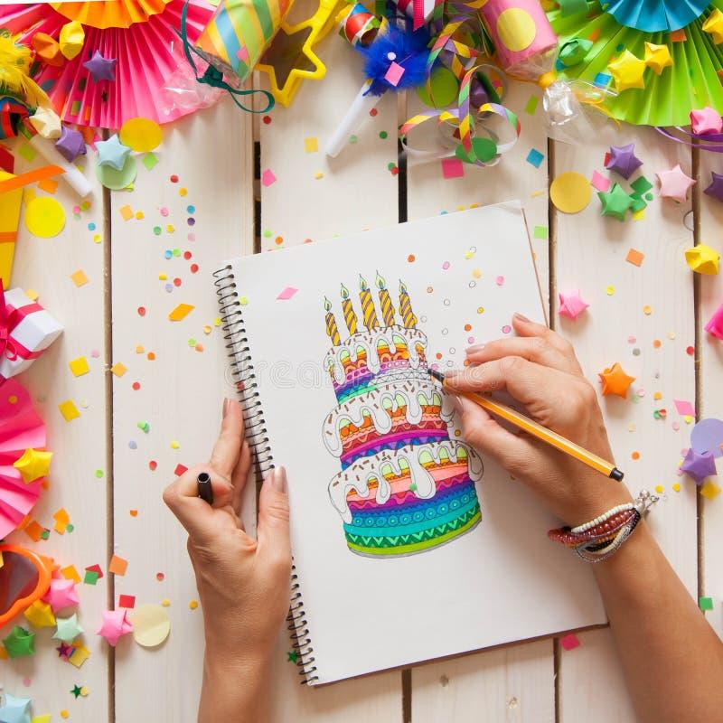 La fille dessine un gâteau avec les marqueurs colorés lumineux Cadeaux, rosett photographie stock libre de droits