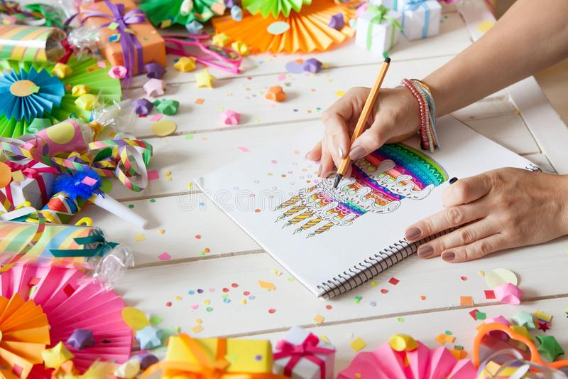 La fille dessine un gâteau avec les marqueurs colorés lumineux Cadeaux, rosett images stock