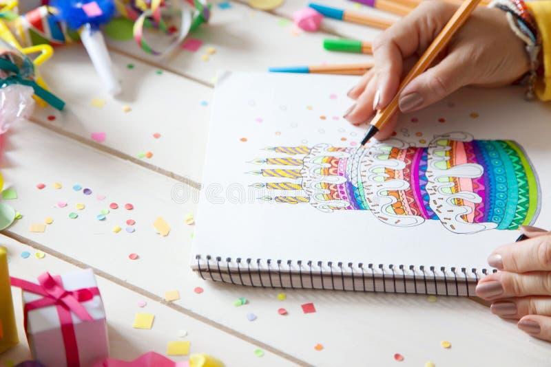 La fille dessine un gâteau avec les marqueurs colorés lumineux Cadeaux, rosett photo libre de droits