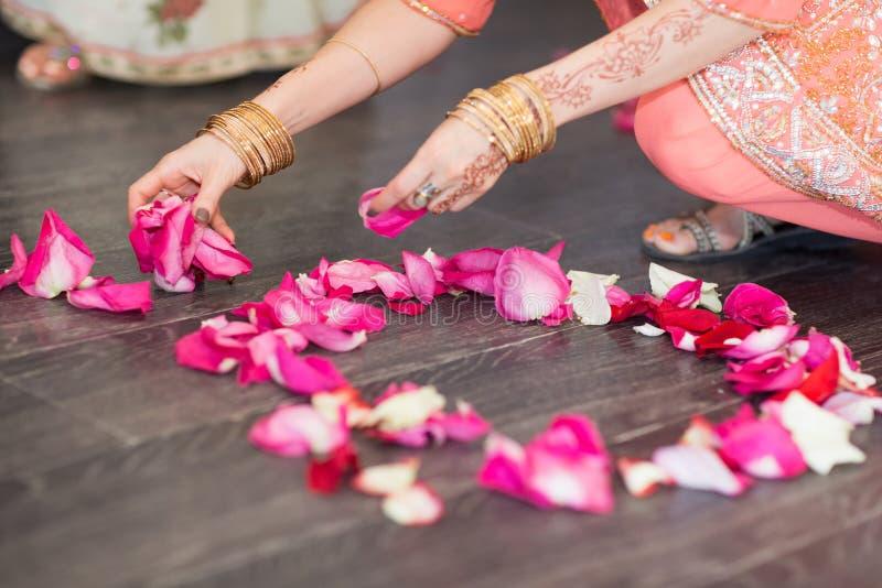 La fille disperse des pétales de rose sur le plancher photographie stock