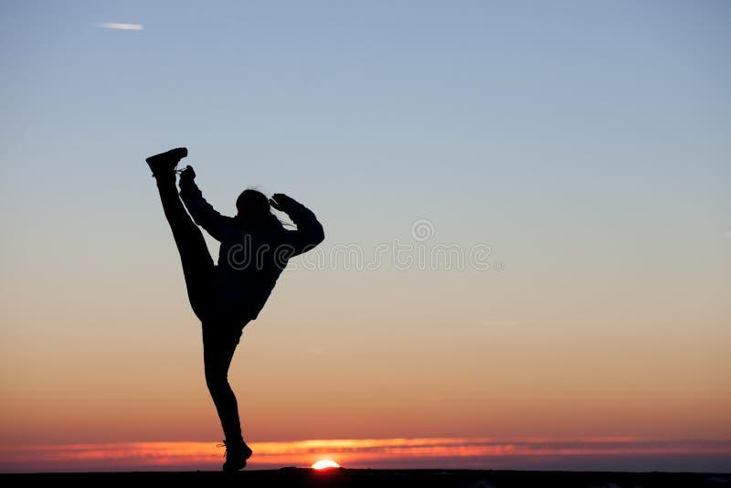 La fille donne un coup de pied sa jambe dans le ciel image stock