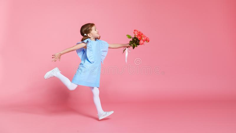 La fille drôle d'enfant court et saute avec le bouquet des fleurs sur la couleur photos libres de droits