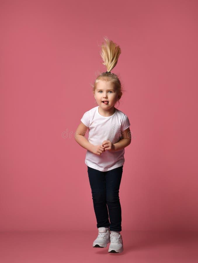 La fille dr?le d'enfant court et saute sur le fond rose images stock