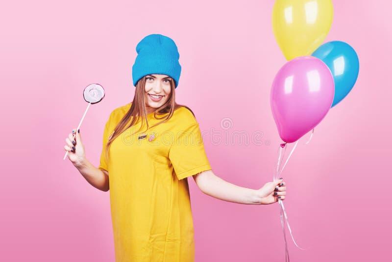 La fille drôle mignonne en portrait de chapeau bleu tient les ballons colorés et la lucette d'un air souriant sur le fond rose Be photos libres de droits