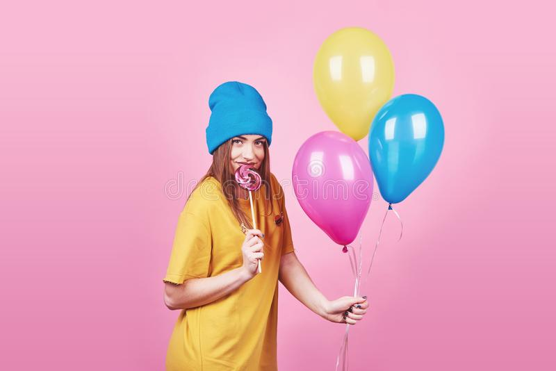 La fille drôle mignonne en portrait de chapeau bleu tient les ballons colorés et la lucette d'un air souriant sur le fond rose Be images stock