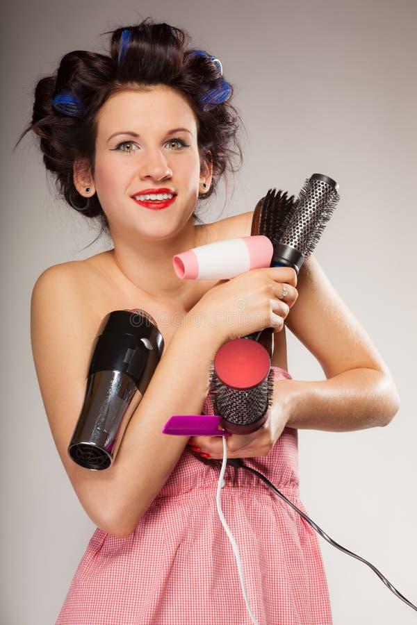La fille drôle dénommant des cheveux tient beaucoup d'accessoires image stock
