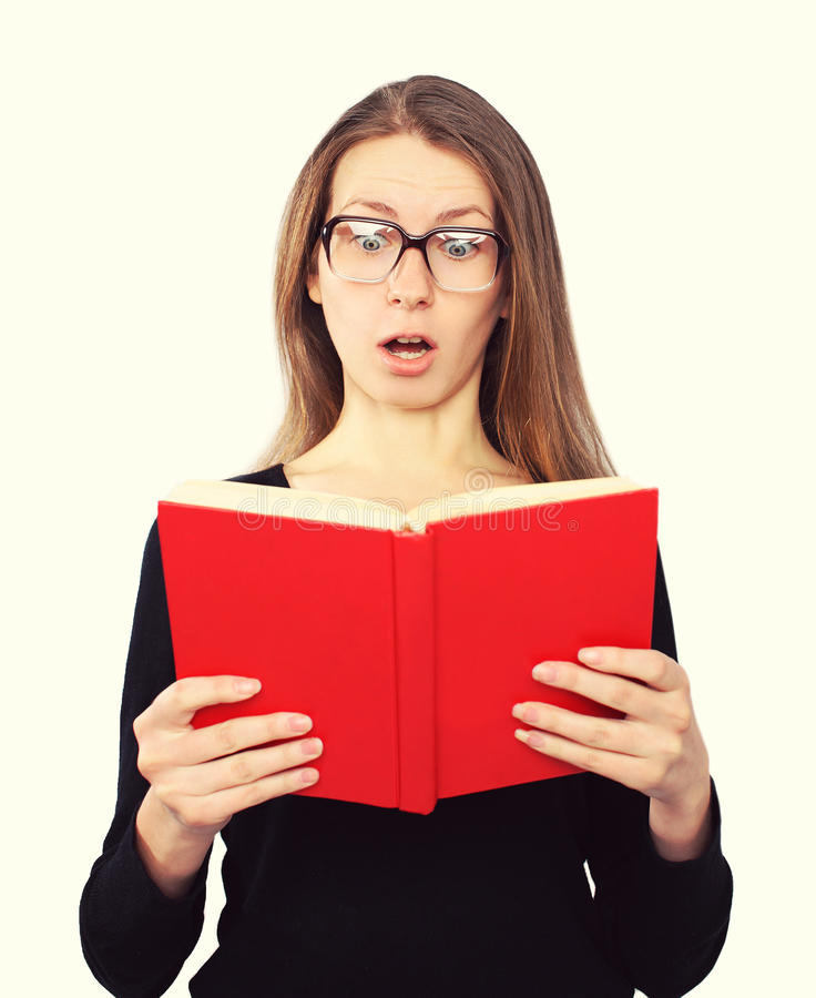 La fille drôle d'étudiant en verres a choqué le regard dans le livre photos stock