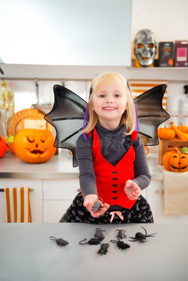 La fille drôle dans le costumein de batte de Halloween avec la souris joue images libres de droits