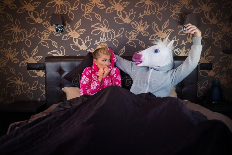 La fille effrayée se trouve avec l'ami drôle dans le masque comique Couples exceptionnels photographie stock