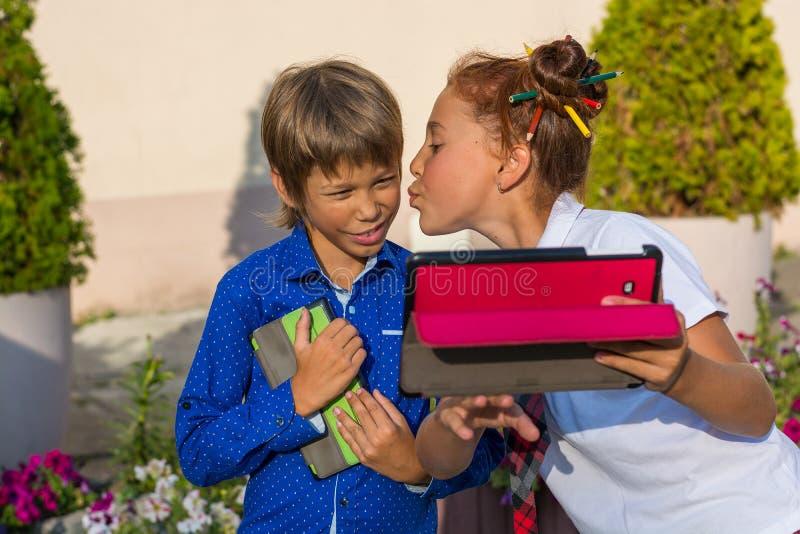 La fille embrasse son jeune frère et fait un selfie sur une table image stock