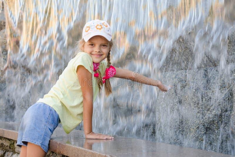La fille en été vêtx avec le sourire étirant sa main pour arroser la cascade artificielle photo stock