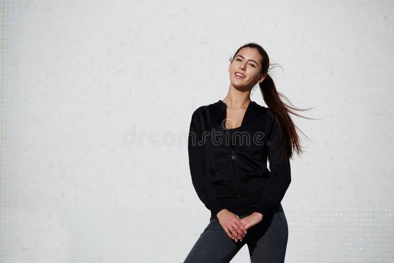 La fille en bonne santé sportive s'est habillée dans les vêtements de sport posant dehors photos stock