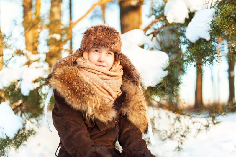 La fille en fourrure chaude d'hiver vêtx contempler le port de forêt d'hiver image libre de droits