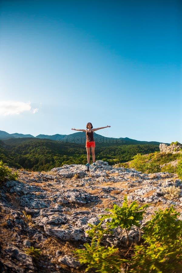 La fille en haut de la montagne a soulevé ses mains  photo stock