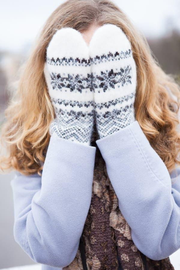 La fille en hiver vêtx a couvert son visage de mitaines de laines images libres de droits