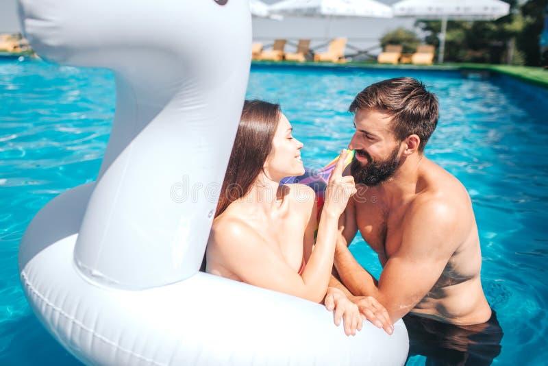 La fille en matelas d'air nage dans la piscine avec l'ami Elle touche son nez Le type regarde la jeune femme et cligner de l'oeil images stock