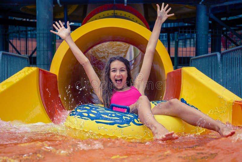 La fille en parc d'aqua ont l'amusement montant sur la glissière d'eau avec l'anneau gonflable photos stock