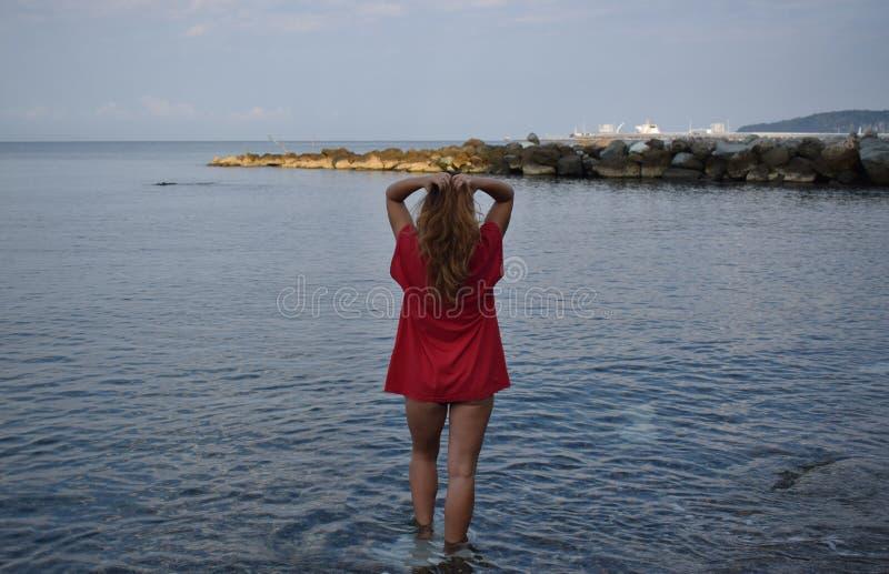 La fille en rouge se tient sur la plage et touche ses cheveux images stock