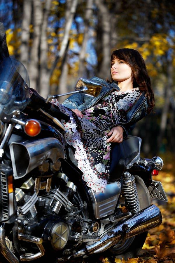La fille en stationnement avec la moto images libres de droits