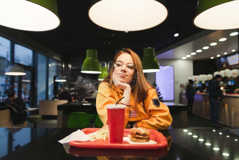 La fille en vêtements décontractés lumineux et verres, s'assied à la table avec un repas dans le restaurant d'aliments de prépara image stock