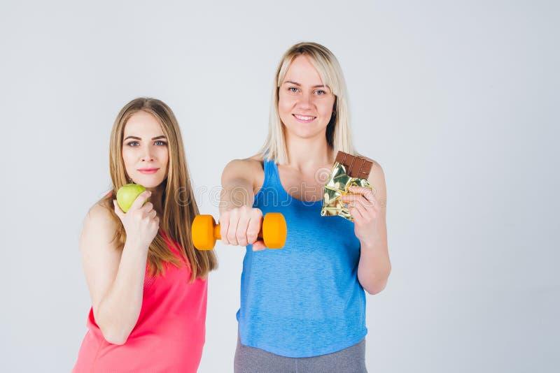 La fille enceinte et son ami mangent d'Apple et d'un chocolat photos stock