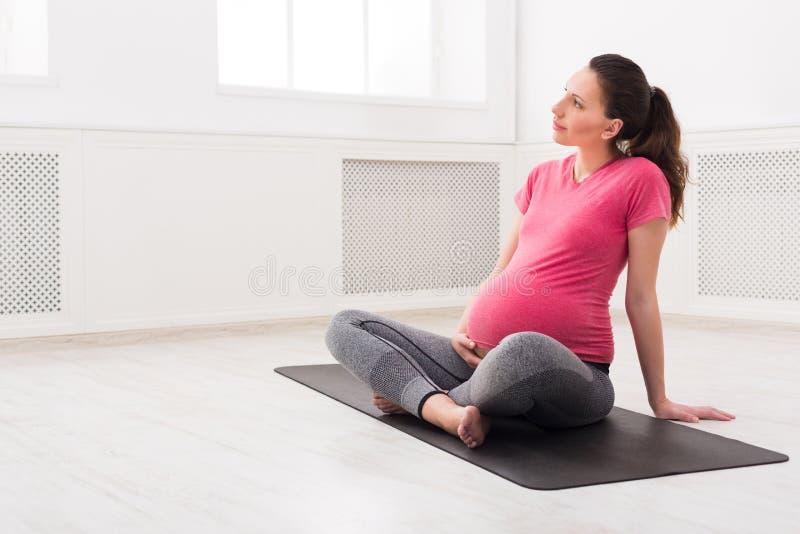La fille enceinte s'asseyant dans la pose de lotus, caressent son ventre photos stock