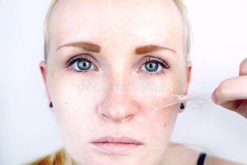 La fille enlève le film de masque du visage Le concept d'enlever la vieille peau sèche, auto-soin photos stock