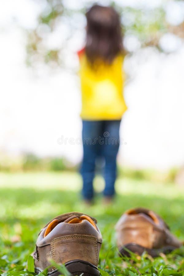 La fille enlèvent ses chaussures Le pied de l'enfant apprend à marcher sur l'herbe images libres de droits