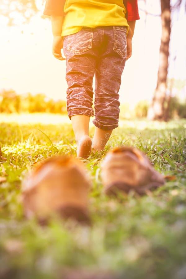 La fille enlèvent ses chaussures Le pied du ` s d'enfant apprend à marcher sur des WI d'herbe photos libres de droits