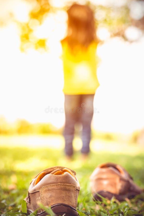 La fille enlèvent ses chaussures Le pied du ` s d'enfant apprend à marcher sur des WI d'herbe images stock