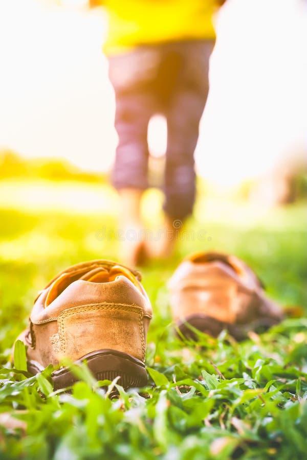 La fille enlèvent ses chaussures Le pied du ` s d'enfant apprend à marcher sur des WI d'herbe photographie stock libre de droits