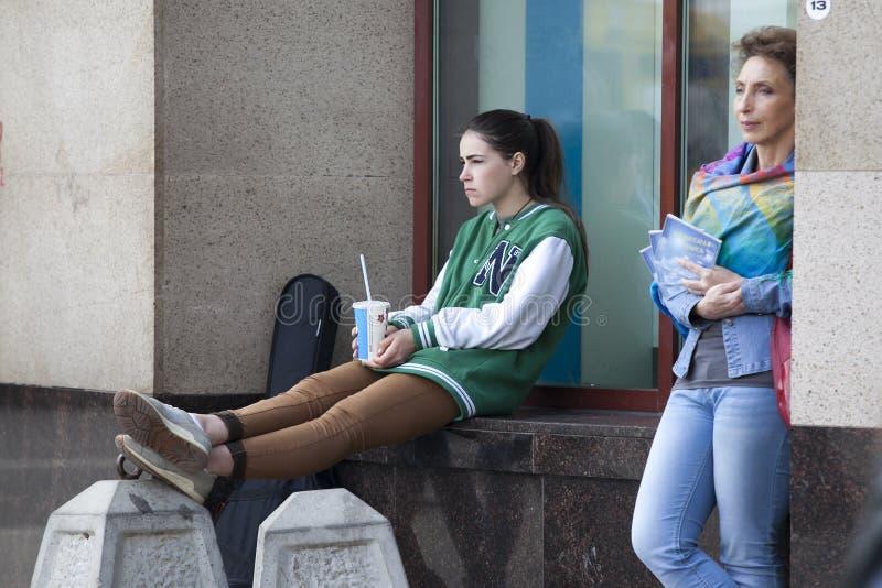 La fille ennuyée s'assied sur le rebord de fenêtre près de la fenêtre sur la rue piétonnière Arbat photographie stock