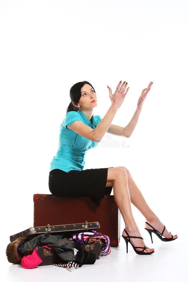 La fille essaye de placer des vêtements dans une vieille valise image libre de droits