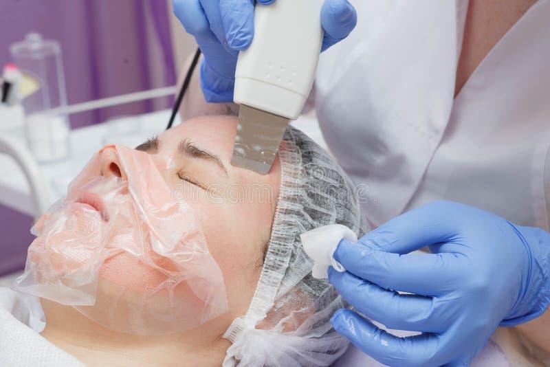 La fille est équipée de service de nettoyage de peau d'ultrason dans le salon de beauté image stock