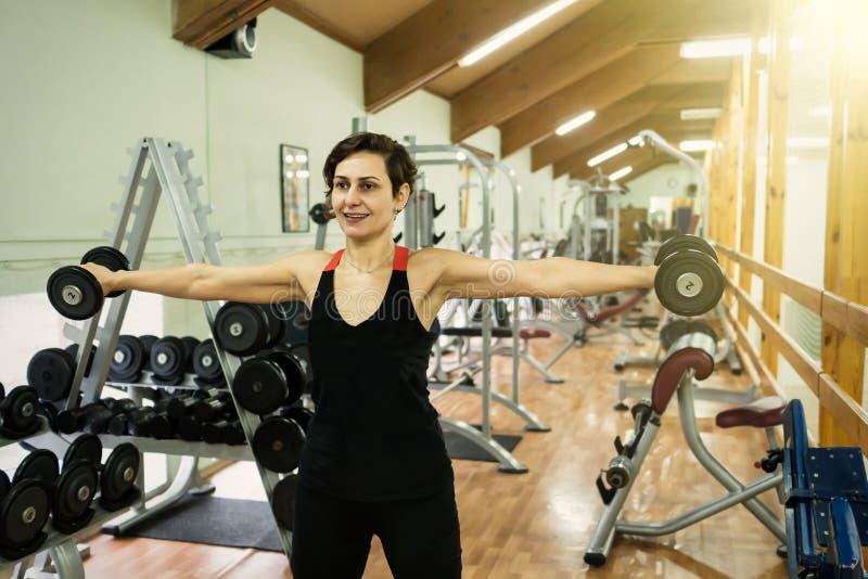 La fille est engagée dans la forme physique dans le gymnase photographie stock libre de droits