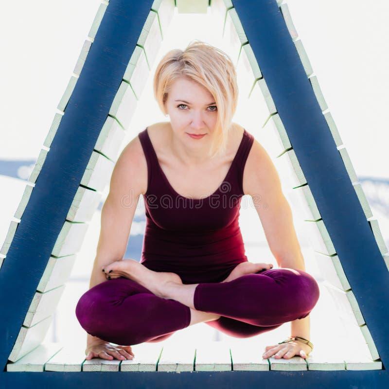 La fille est engagée dans le yoga dans un chiffre triangulaire images libres de droits