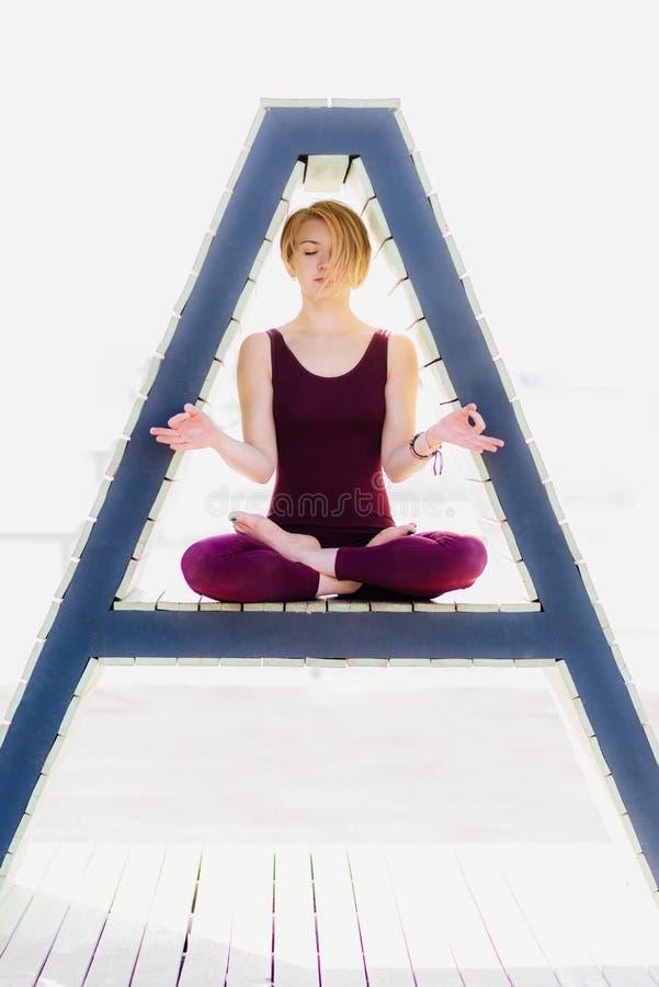 La fille est engagée dans le yoga dans un chiffre triangulaire photo libre de droits