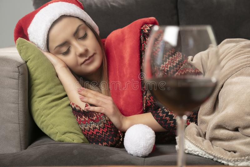 La fille est tombée endormi sur le divan, Noël de attente, vin sur la table image stock
