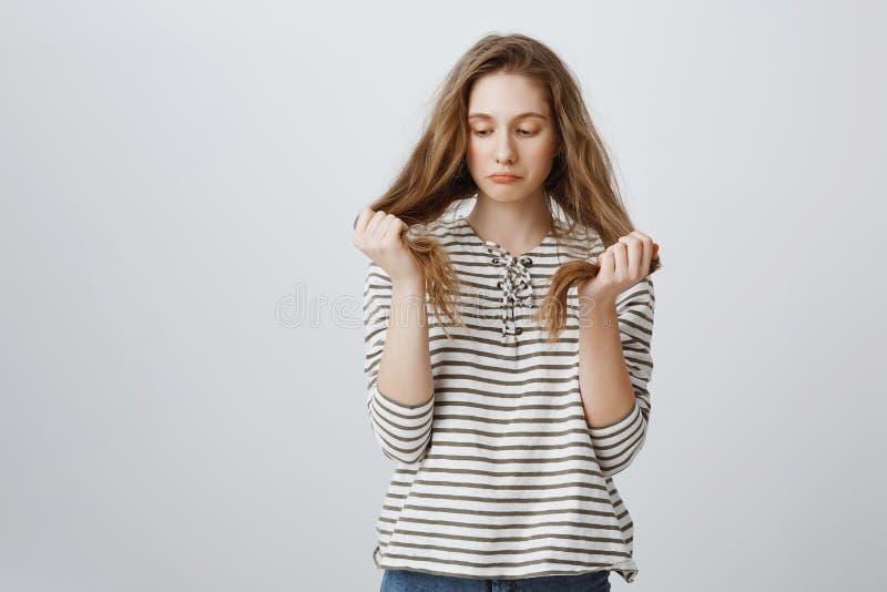 La fille est triste de ses mauvaises mèches de cheveux Portrait de la jeune femme tracassée sombre tenant des cheveux et étant dé photo libre de droits