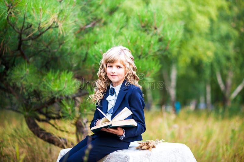 La fille est une première niveleuse s'asseyant à une table et tenant un livre ouvert dans des ses mains Une écolière dans un cost photo libre de droits