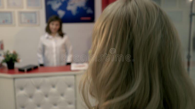 La fille est venue à la cosmétologie, elle est saluée cordialement par le docteur, dit quelque chose et demande à signer quelques images stock