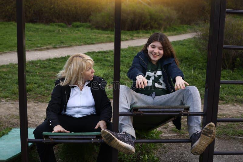 La fille et la femme de l'adolescence s'exercent sur l'endroit extérieur de gymnase en parc de ville photos stock